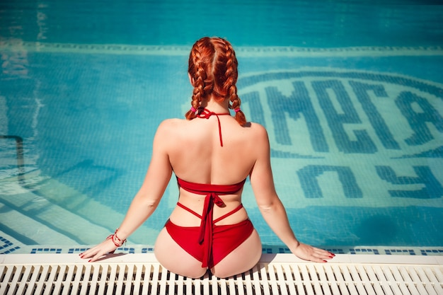 Colorful portrait of pretty young woman in red swimsuit lying near swimming pool