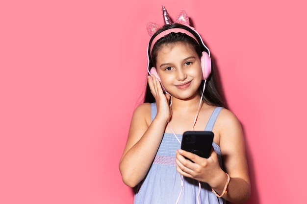 Colorful portrait of smiling little child girl, holding smartphone and listening the music with headphones on studio background of pastel pink color with copy space.