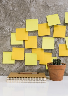 Colorful post it,memo notebook,pencil,cactus in flowerpot on white desk concrete background,work space concept