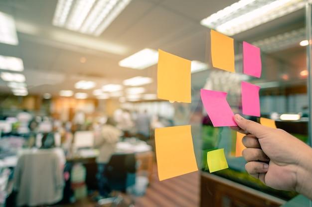 ガラスに貼り付けるカラフルなポストイットリストと手渡しのテキストを入れるためのコピースペースがあります