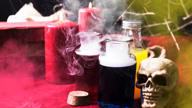 Colorful potions and candles with halloween decorations