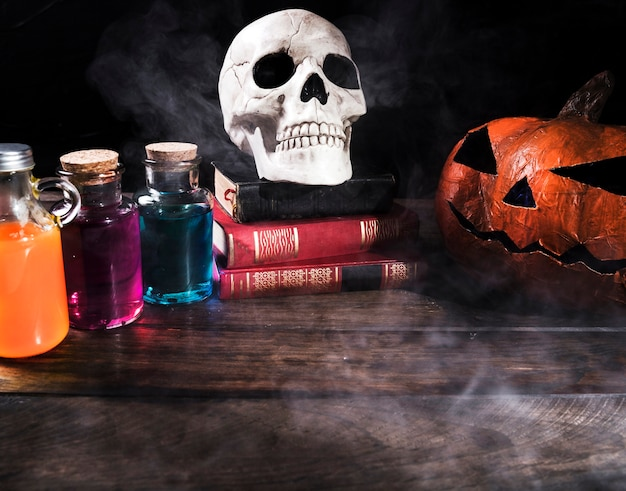Colorful potions with pumpkin on table