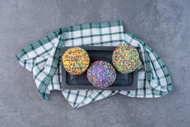 Разноцветные пралине, украшенные посыпкой на черной тарелке.