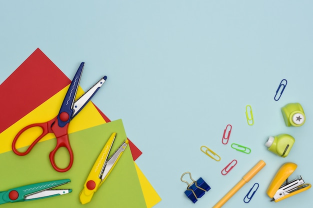 Colorful preschool education and hobbies flat lay. stationary items for creativity. curly scissors, pen, paperclip, punch