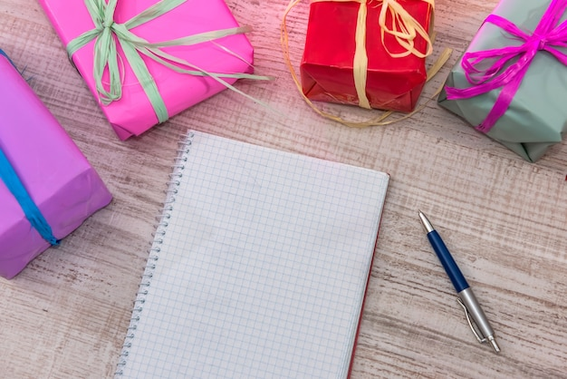Colorful present boxes with opened notepad. new year's planning. new beginning