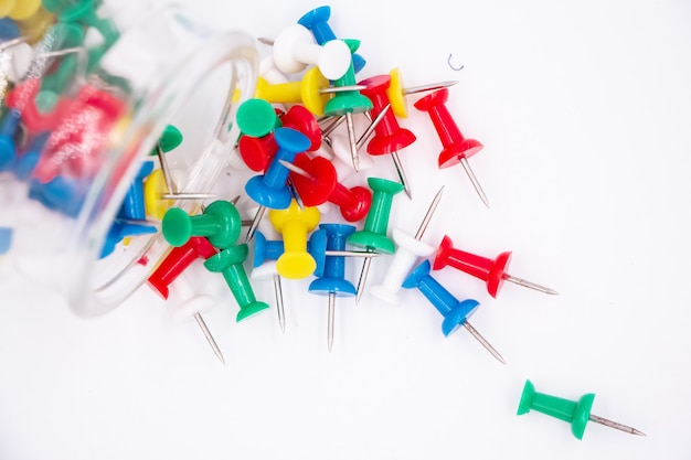 The colorful push pins put on white background, blurry light around