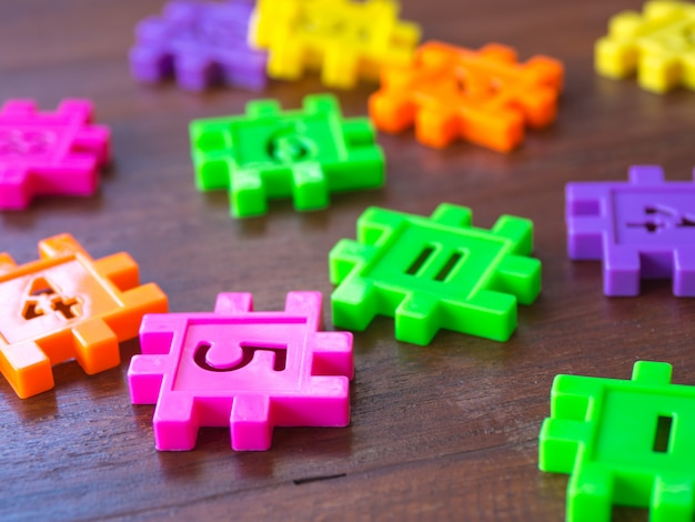 Colorful puzzle jigsaw plastic number on the wooden table. concept of education and math learning