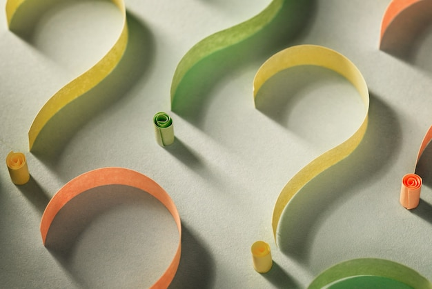 Colorful question marks of curled paper tape side lit with shadow on a white background