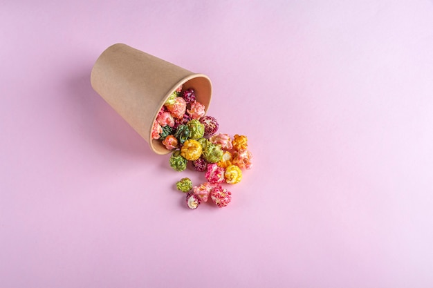 Colorful rainbow caramel candy popcorn on dark background. cinema snack concept. food for watching movie and entertainment. copy space for text, flat lay.