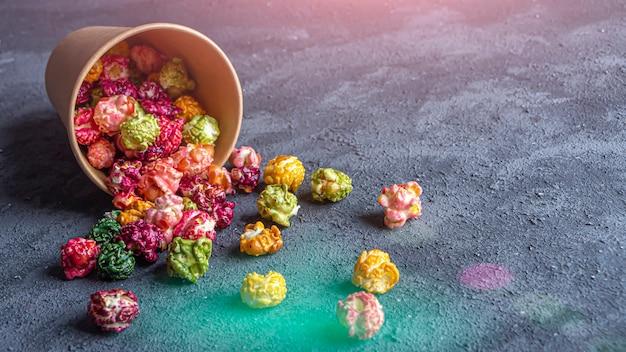 暗い背景にカラフルなレインボーキャラメルキャンディーポップコーン。シネマスナックのコンセプト。映画や娯楽を見るための食べ物。テキスト用のスペースをコピーし、フラットレイ。