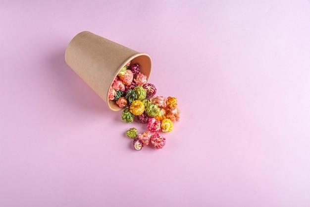 暗い背景にカラフルなレインボーキャラメルキャンディーポップコーン。シネマスナックのコンセプト。映画や娯楽を見るための食べ物。テキスト用のコピースペース、フラットレイ。