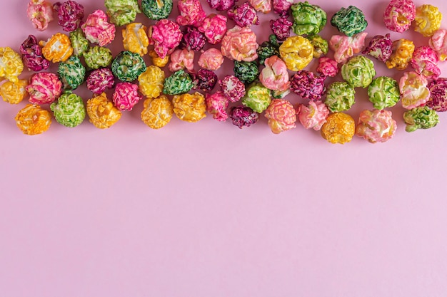 ピンクの背景にカラフルなレインボーキャラメルキャンディーポップコーン。シネマスナックのコンセプト。映画やエンターテインメントの背景を見ています。テキスト用のスペースをコピーし、フラットレイ。