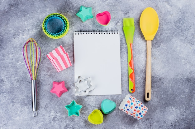 Colorful rainbow kitchen utensils and empty notebook on concrete background. copy space