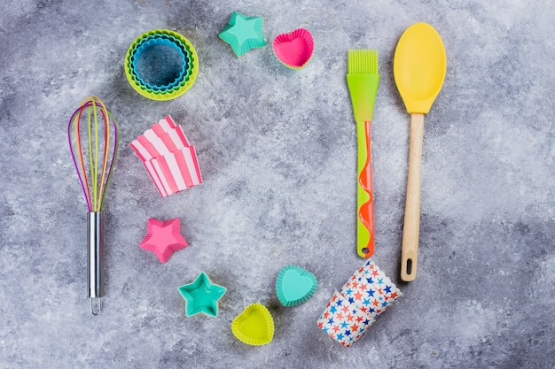 Colorful rainbow kitchen utensils on grey concrete table background. top view, copy space