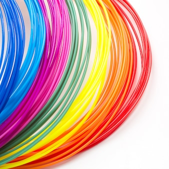 Colorful rainbow plastic filaments for 3d pen laying on white