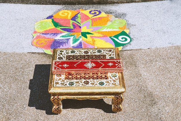 Colorful rangoli art and chantry on the floor during indian wedding ceremony