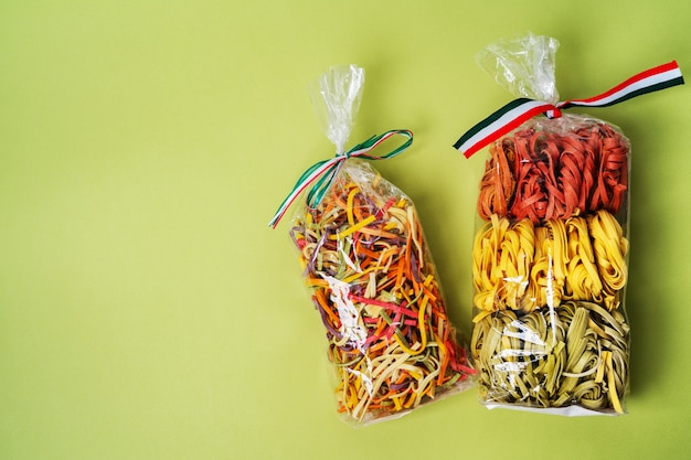 Colorful raw italian pasta in transparent plastic bag on green background. homemade colored pasta.