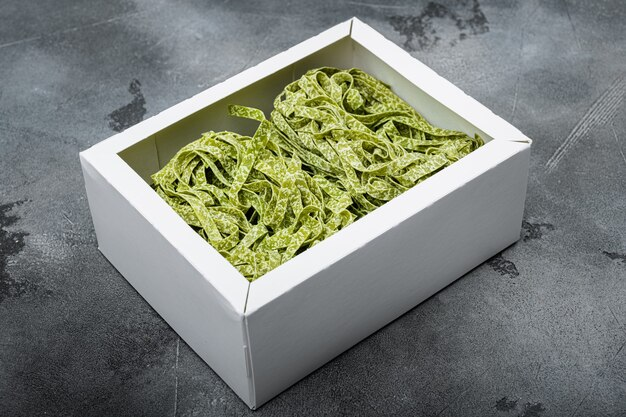 회색 돌 탁자 배경에 있는 상자 세트의 다채로운 생 이탈리아 탈리아텔레 파스타