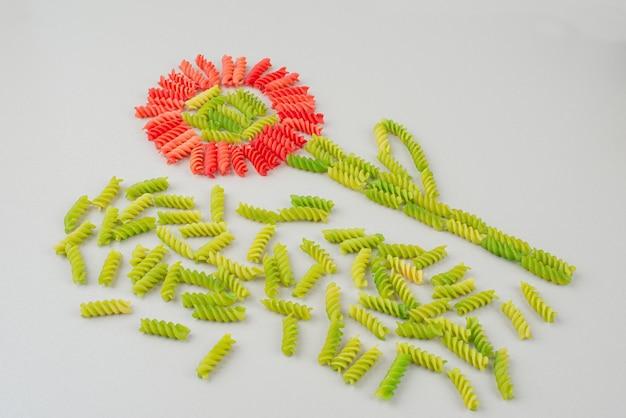 Maccheroni crudi colorati come un fiore su bianco