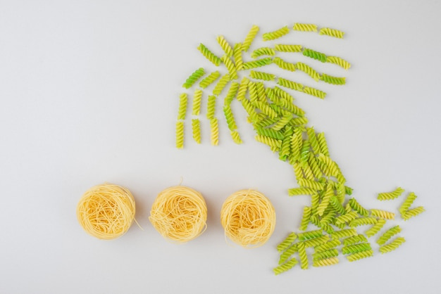 Colorful raw macaroni as a palm on white surface