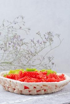 Maccheroni crudi colorati sulla piastra con fiore appassito