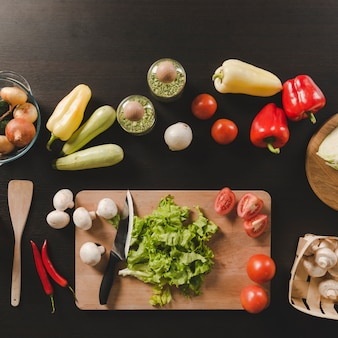 Colorful raw vegetables on black kitchen counter