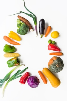 Colorful raw vegetables forming frame on white surface