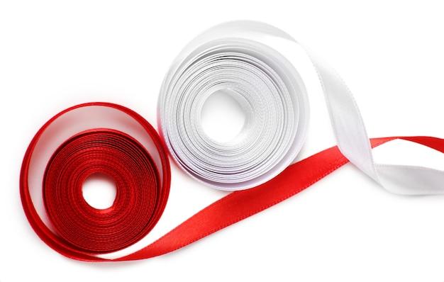 白で隔離されるカラフルな赤と白のリボン