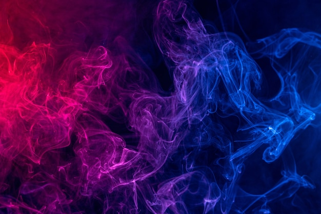 Colorful red and blue color smoke isolated on dark black background