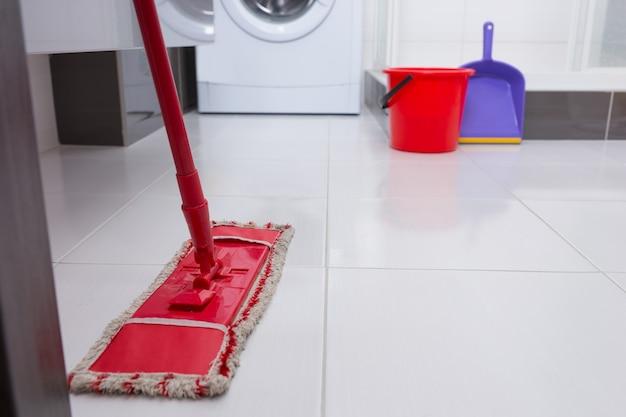 後ろに洗濯機が見えるバスルームまたはランドリーの白いタイル張りの床にカラフルな赤いモップ、低角度のクローズアップビュー