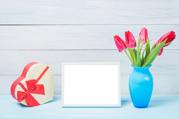 Colorful red spring tulip flowers in nice blue vase and blank photo frame with decorative heart giftbox on light wooden background
