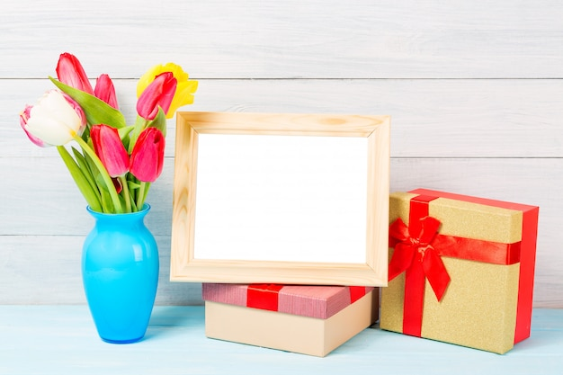 Colorful red spring tulip flowers in nice blue vase and blank photo frame with giftboxes on light wooden background