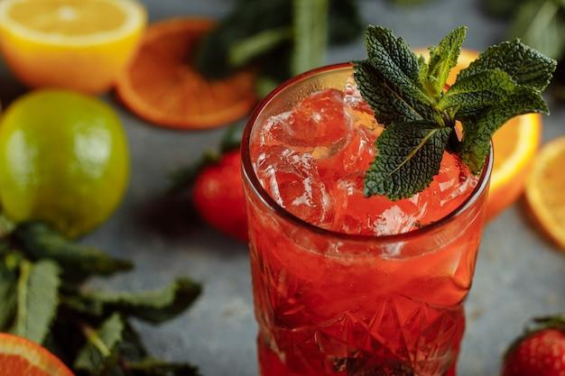 Яркие освежающие напитки на лето, холодный клубничный лимонад с кубиками льда в бокалах, украшенный нарезанными свежими лимонами.