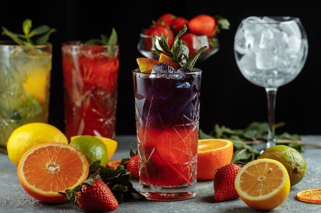 夏に向けたカラフルでさわやかなドリンク、スライスした新鮮なレモンを添えたグラスに角氷を入れた冷たいストロベリーレモネードジュース。