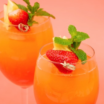 Colorful refreshing strawberry orange sunrise cocktail drinks in the glasses