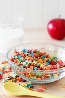 子供のための牛乳と赤いリンゴとカラフルな米シリアル。健康的な簡単な朝食。