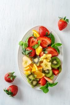 Красочные спелые фрукты и ягоды на блюде, вид сверху на белом фоне. концепция вегетарианской пищи. клубника, киви, яблоко и апельсины.