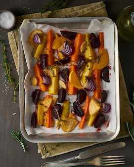 Colorful roasted vegetables on tray with parchment. mix of carrots, beets, turnips, rutabaga, onions