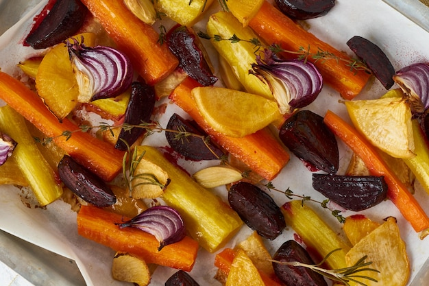 Colorful roasted vegetables on tray with parchment. mix of carrots, beets, turnips, rutabaga