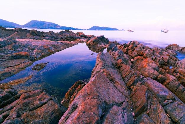 다채로운 바위와 해변에 부서 지는 파도 큰 다채로운 돌입니다.