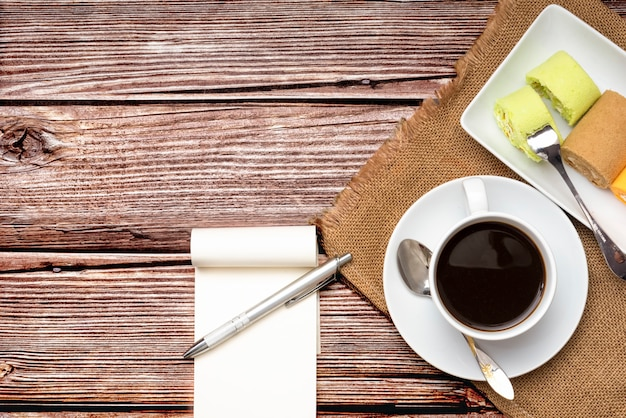 Colorful roll cakes and coffee notebook with pen on pattern wood background