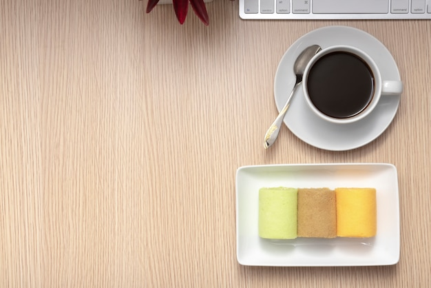 Colorful roll cakes and coffee on pattern wood background