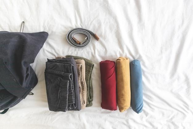 Красочные рулоны футболки на концепции белой кровати готовы к путешествию.
