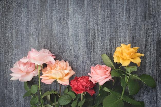 灰色の木製の表面にカラフルなバラ