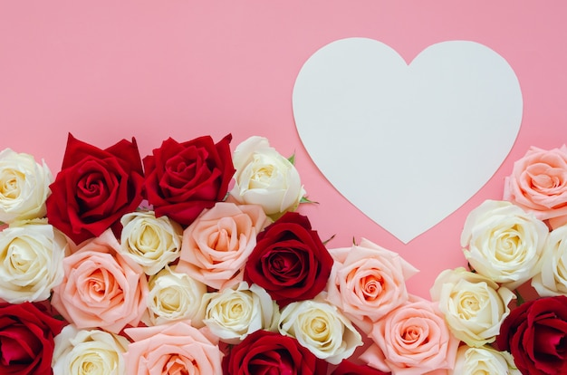 Colorful roses and paper heart on pink