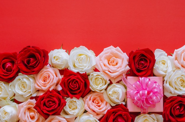 Colorful roses and present on red