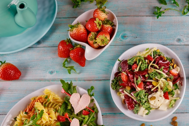 Colorful rotini pasta with healthy spring salad and fresh strawberries