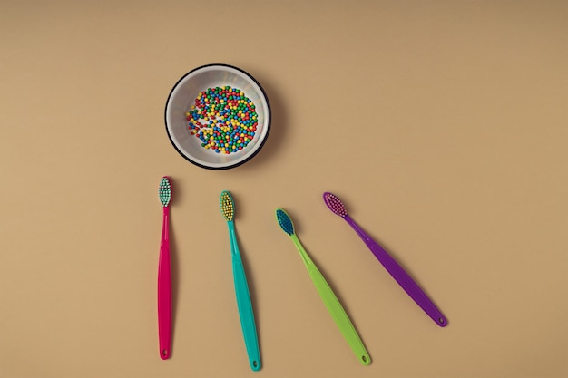 Colorful round ball sprinkles in a white small bowl on yellow paper background and four different colour vibrant toothbrushes. creative dental care and healthy sugar consumption concept.