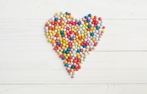 Красочные круглые конфеты, лежащие в форме сердца на белом деревянном фоне