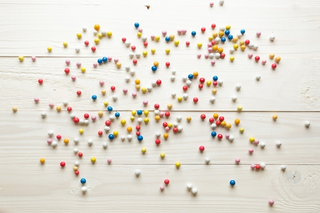 Colorful round candies lying on white wooden boards